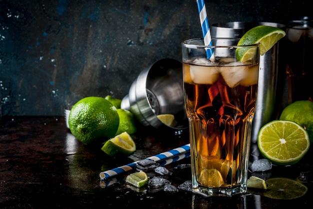 Cuba libre, cocktail long island ou thé glacé avec alcool fort, cola, citron vert et glace, deux verres, fond sombre