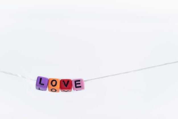 Cube alphabet anglais coloré avec mot amour accroché sur une chaîne avec du papier blanc