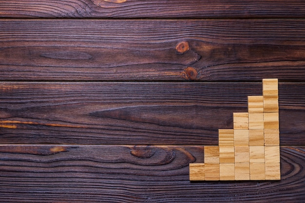 Un cube de blocs de bois sur un fond texturé en bois noir
