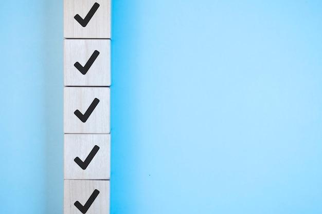 Cube en bois avec coche sur fond bleu, concept de liste de contrôle, espace de copie.