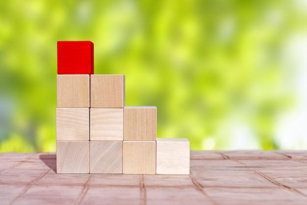 Cube de bois disposé en forme de pyramide, concept d'entreprise. le cube supérieur est rouge
