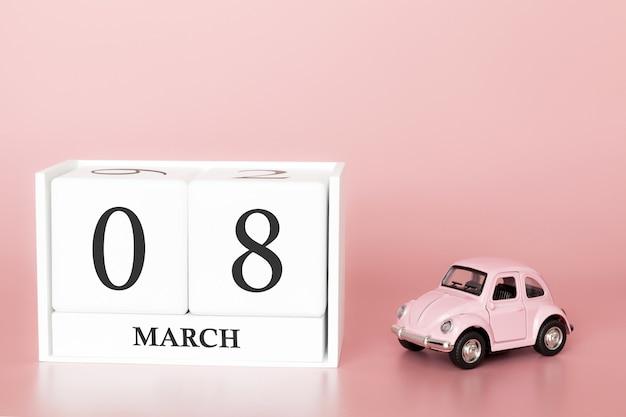 Cube en bois du 8 mars. jour 8 du mois de mars, calendrier sur fond rose avec voiture rétro.