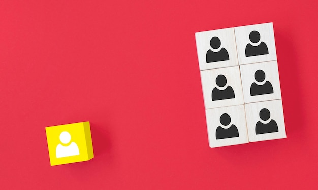 Cube en bois jaune avec l'icône de la personne se démarquer de la foule sur fond bleu