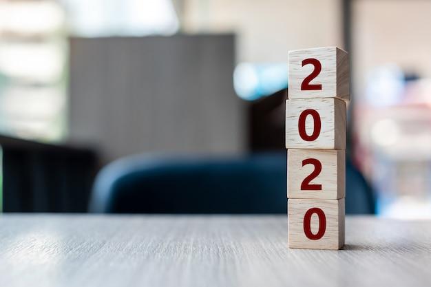 Cube en bois avec mot 2020 sur fond de tableau.