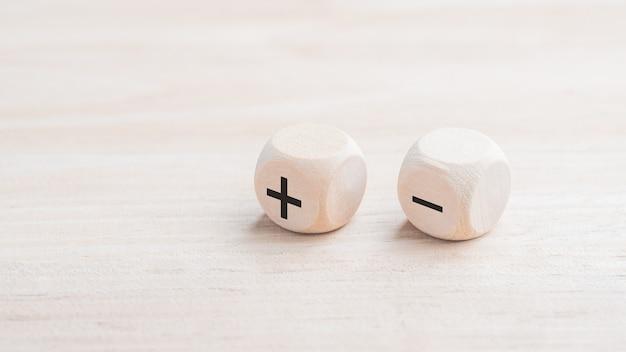 Cube en bois plus avec un symbole moins. concept d'avantages et d'inconvénients.