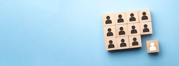 Un cube en bois rouge avec une icône de personne se démarque de la foule sur une surface bleue