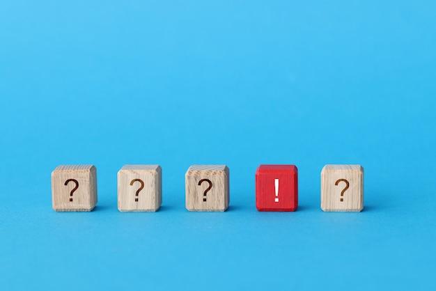 Cube en bois rouge avec point d'exclamation se trouvant parmi les cubes avec gros plan de points d'interrogation. résoudre