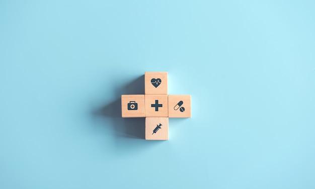 Cube de bois avec symbole médical sur fond bleu pastel.