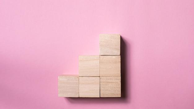 Cube de bois vierge maquette en forme d'escalier sur rose