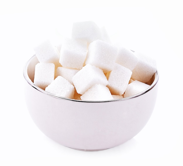 Cube de sucre dans un bol sur fond blanc