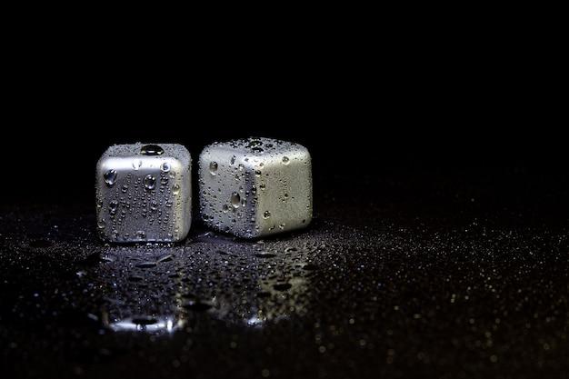 Cubes en acier inoxydable simulant de la glace pour refroidir les boissons sur une surface noire avec un reflet.