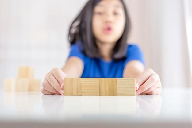 Cubes de blocs de bois vierges sur table avec une fille asiatique floue en arrière-plan