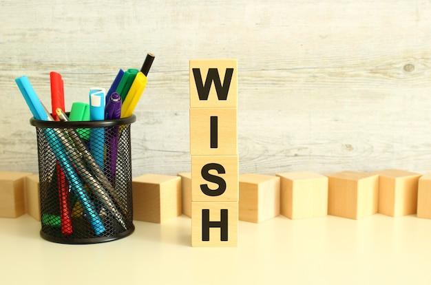 Cubes en bois empilés avec des lettres wish sur une table de travail blanche sur un fond gris texturé.
