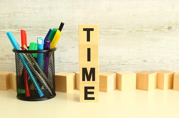 Cubes en bois empilés avec le temps des lettres sur une table de travail blanche sur un fond gris texturé