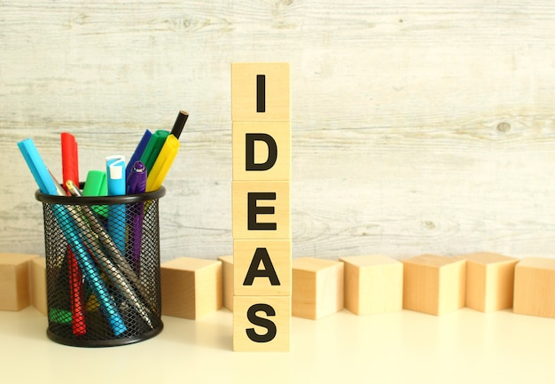 Cubes en bois empilés verticalement avec des lettres du mot idées sur une table de travail blanche sur fond gris texturé. concept d'entreprise