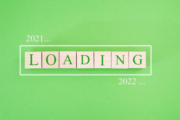 Cubes en bois sur fond vert. chargement de 2021 à 2022.