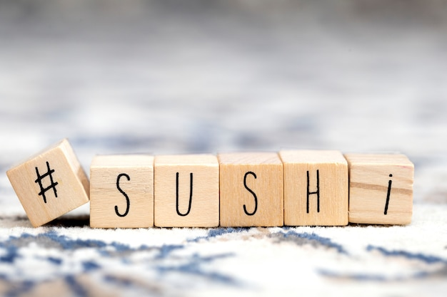 Cubes en bois avec un hashtag et le mot sushi, médias sociaux et concept alimentaire