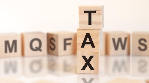 Cubes en bois avec impôt sur les lettres disposés en pyramide verticale, fond blanc, reflet de la surface de la table, concept d'entreprise