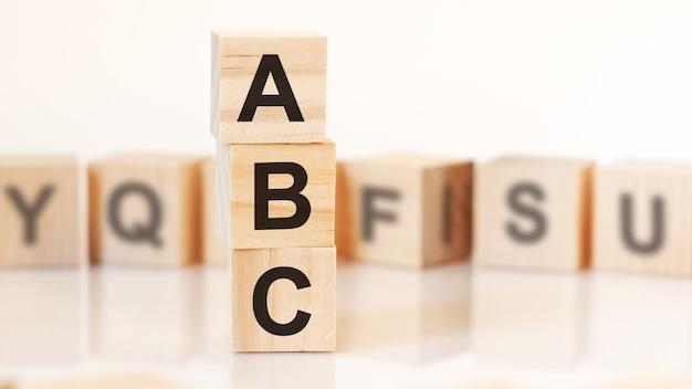 Cubes en bois avec lettres abc disposés en pyramide verticale, fond blanc, reflet de la surface de la table, concept d'entreprise. abc - abréviation de toujours ferme.