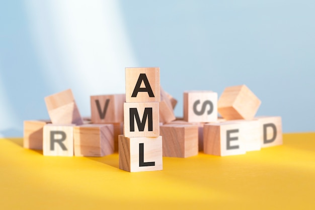 Cubes en bois avec lettres aml disposés en pyramide verticale, fond jaune