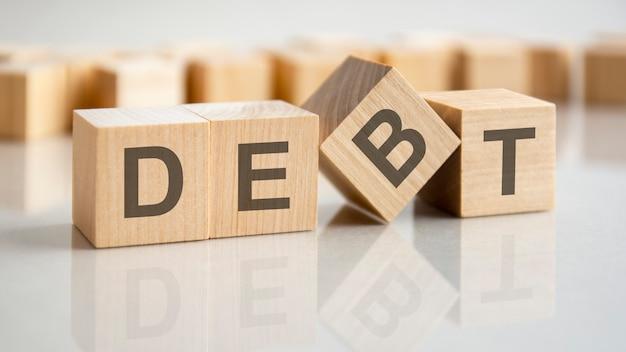 Cubes en bois avec les lettres de la dette sur la surface lumineuse d'une table grise, concept d'entreprise.