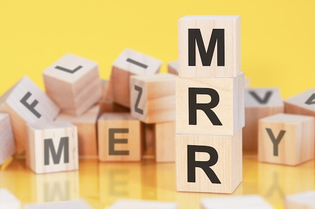 Cubes en bois avec lettres mrr disposés en pyramide verticale, fond jaune, reflet de la surface de la table, concept d'entreprise, mrr - abréviation de monthly recurring revenue