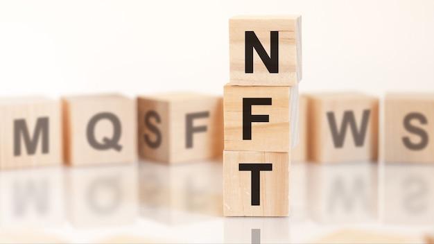 Cubes en bois avec des lettres nft disposées en pyramide verticale, sur fond clair, surface de réflexion, concept d'entreprise. nft abréviation de jeton non fongible