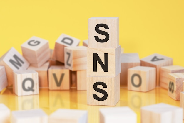 Cubes en bois avec lettres sns disposés en pyramide verticale, fond jaune, reflet de la surface de la table, concept d'entreprise, sns - abréviation de service de réseautage social