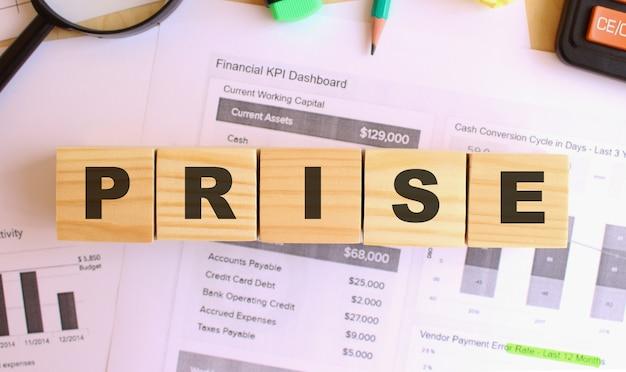 Cubes en bois avec des lettres sur la table au bureau. texte prix. concept financier.