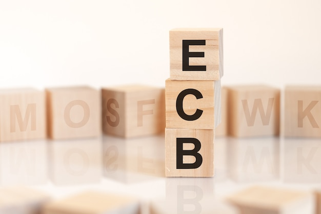 Cubes en bois avec mot ecb disposés en pyramide verticale, sur la surface lumineuse est une rangée de cubes en bois avec des lettres