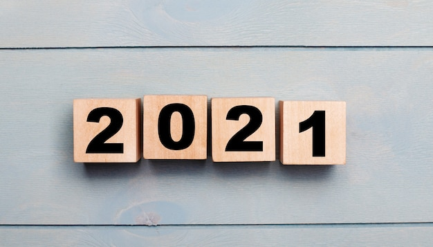 Cubes en bois avec numéros 2021 sur un fond en bois bleu clair. concept de nouvel an