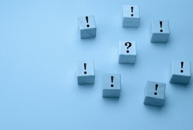 Cubes en bois avec des points d'exclamation et un point d'interrogation au milieu sur une surface bleu clair