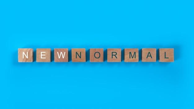 Cubes en bois pour une nouvelle formulation normale. le monde est en train de changer pour l'équilibrer en une nouvelle normalité, notamment les affaires, l'économie, l'environnement et la santé.