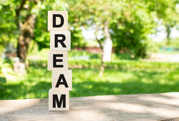 Des cubes en bois sont empilés verticalement sur une table en bois dans le jardin. le mot dream est écrit en lettres noires. concept pour votre conception