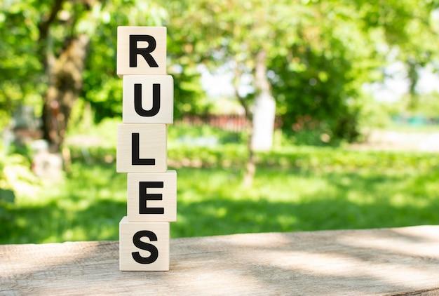 Les cubes en bois sont empilés verticalement sur une table en bois dans le jardin le mot règles est écrit en bla