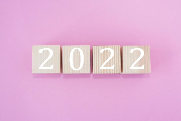 Cubes en bois avec le texte 2022 sur fond rose, le début de la nouvelle année.