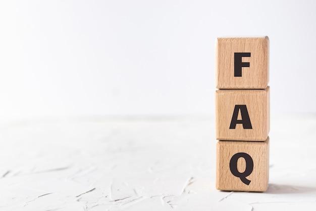 Cubes en bois avec texte faq sur fond de texture mastic blanc. questions fréquemment posées. mise à plat, vue de dessus.