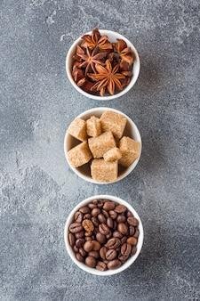 Cubes de cassonade, grains de café et anis étoilé sur fond de béton.