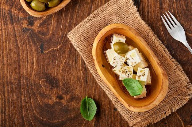Cubes de fromage feta au romarin, olives et sauce à l'huile d'olive dans un bol sur la vieille table en bois brun. fromage maison grec traditionnel.