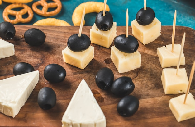 Cubes de fromage et olives noires sur une planche de bois avec des craquelins