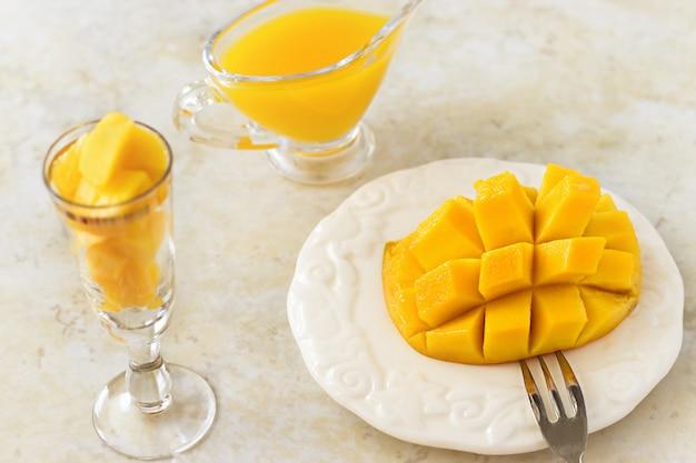 Cubes de fruits mangue et purée de jus de mangue sur fond blanc de béton.