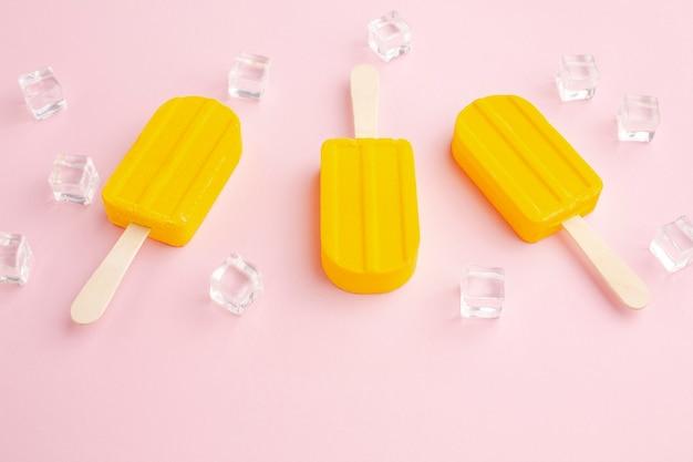 Cubes de glace à côté de la crème glacée sur bâton