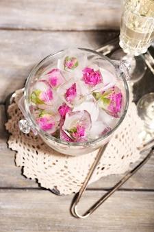 Cubes de glace avec des fleurs roses dans un seau en verre et deux verres de champagne sur table en bois