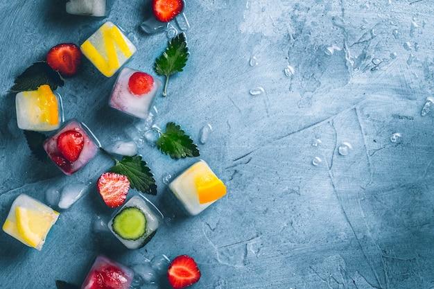 Cubes de glace avec des fruits et de la glace cassée sur un fond bleu pierre avec des feuilles de menthe et des fruits frais. menthe, fraise, cerise, citron, orange. mise à plat, vue de dessus