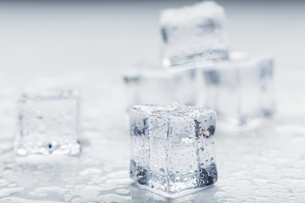 Cubes de glace avec des gouttes d'eau dispersées sur un fond blanc, vue de dessus. glace rafraîchissante.