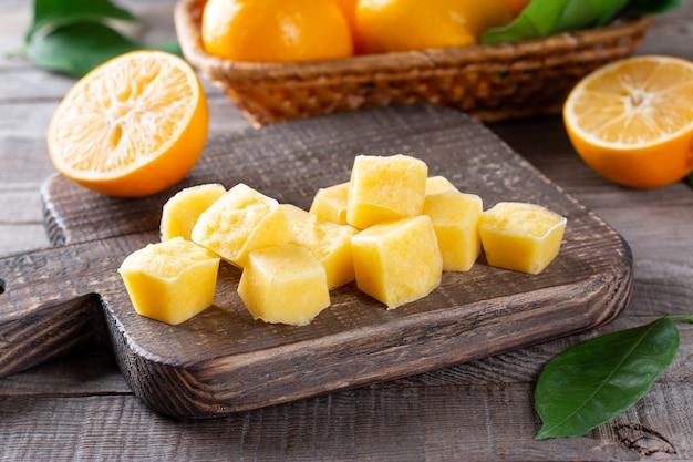 Cubes de jus de citron congelé sur une table en bois, gros plan