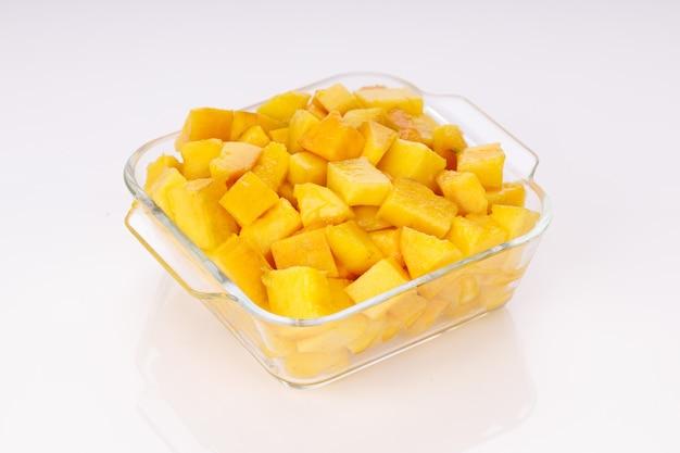 Cubes de mangue mûre ou morceau coupé disposés dans un récipient carré en verre avec un fond de couleur blanche.