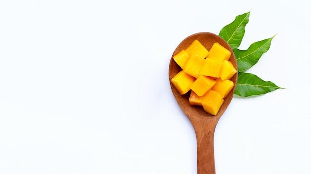 Cubes de mangue mûre en tranches sur une cuillère en bois sur fond blanc.