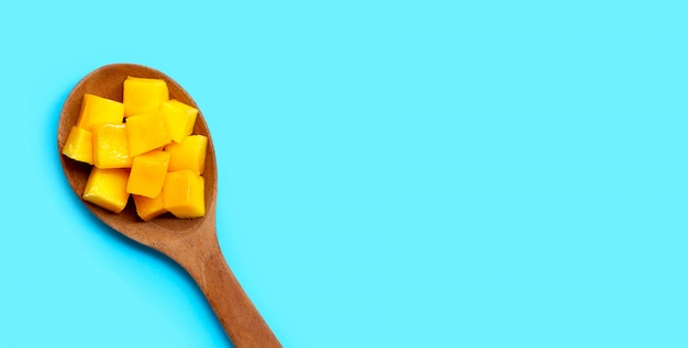 Cubes de mangue mûre en tranches sur une cuillère en bois sur fond bleu.