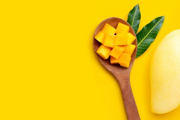 Cubes de mangue mûre en tranches sur une cuillère en bois sur fond jaune.
